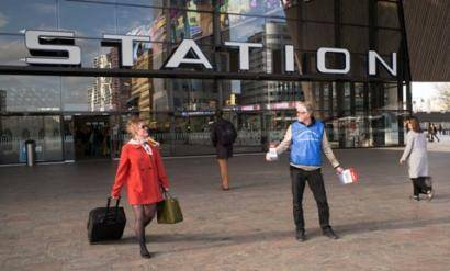 photo of volunteer handing out campaign leaflets at Rotterdam train station