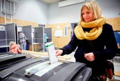photo of woman putting her ballot in ballot box